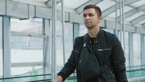 Un jeune homme sûr avec un sac à main dans le terminal d'aéroport moderne banque de vidéos