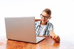 Un jeune homme s'asseyant à une table avec un ordinateur portable et une dactylographie, au service de mini-messages ou à parler  photos stock