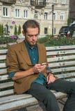 Un jeune homme s'asseyant avec le téléphone portable Photographie stock