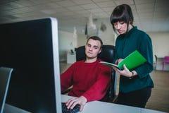 Un jeune homme s'assied à l'ordinateur dans sa chaise et jeune femme se tenant à côté de lui et à l'exposition quelque chose dans images stock