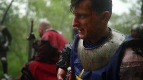 Un jeune homme s'assied dans l'image d'un chevalier m?di?val dans l'armure et nettoie son ?p?e banque de vidéos