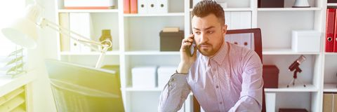 Un jeune homme s'assied dans le bureau, parle au téléphone et travaille sur l'ordinateur photo stock