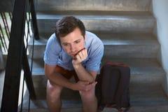 Un jeune homme s'assied sur les escaliers et triste Il a perdu les clés à l'appartement, Photographie stock