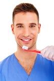 Un jeune homme se brossant les dents d'isolement sur le fond blanc Images stock