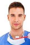 Un jeune homme se brossant les dents d'isolement sur le fond blanc Photo stock