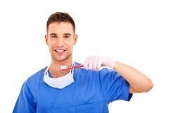 Un jeune homme se brossant les dents d'isolement sur le fond blanc Image stock