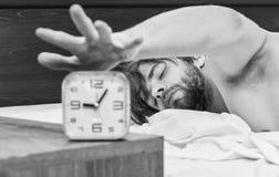 Un jeune homme se r?veillant dans le lit et ?tirant ses bras Homme s'?tirant dans le lit R?veillez les hommes de matin photo stock