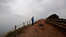 Un jeune homme se tient sur la route abandonnée images stock