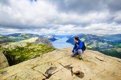 Un jeune homme sur la vue admirative de montagne au-dessus de Lysefjord norway Photographie stock libre de droits
