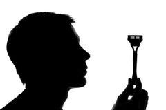 Un jeune homme tenant une verticale de rasoir - silhouette Image libre de droits