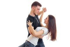 Un jeune homme tient l'amie et les astuces il en plan rapproché de danse Photo libre de droits