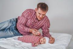 Un jeune homme tient la poignée d'un fils nouveau-né sur le fond blanc Photo stock