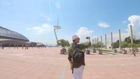 Un jeune homme, touriste se tenant avec un sac à dos et dans un chapeau et tirant une vidéo par le smartphone près de la tour de  banque de vidéos