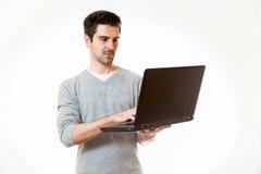 Un jeune homme travaille sur un ordinateur portable tout en se tenant Images stock