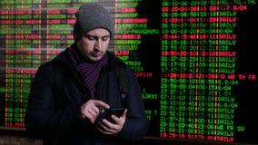 Un jeune homme utilise un smartphone d'un panneau électronique de l'arrivée des vols, trains clips vidéos