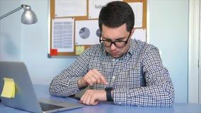 Un jeune homme utilise une montre intelligente pour vérifier les messages entrants à son téléphone portable banque de vidéos