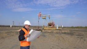 Un jeune ingénieur caucasien dans un gilet de signal et regards de casque de protection au diagramme du pompage de pétrole, de ga banque de vidéos
