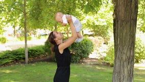 Un jeune jeu heureux de mère avec un bébé nouveau-né par temps chaud en parc banque de vidéos