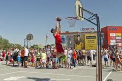 Un jeune joueur de basket exécute un jet au claquement trempent le cont images stock