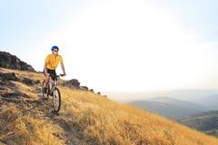 Un jeune mâle conduisant un vélo de montagne sur un coucher du soleil Image stock