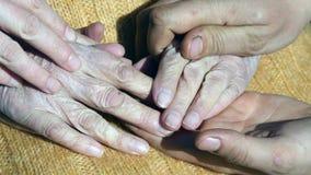 Un jeune mâle et des mains femelles soulageant une vieille paire de mains extérieures Photo libre de droits