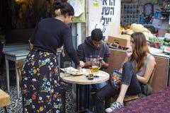 Un jeune mâle juif à une table de café à Jérusalem Israël utilisant son téléphone portable tandis que son amie attend patiemment Photographie stock libre de droits