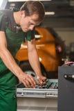 Un jeune mécanicien choisit des outils de boîte pour la réparation de voiture image libre de droits