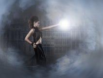 Un jeune magicien de brunette moulant une bille de foudre Images stock
