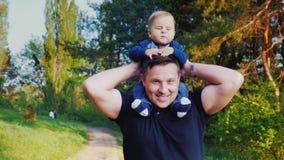 Un jeune père caucasien porte son fils sur ses épaules Ensemble ils marchent en parc Vidéo de steadicam de mouvement lent banque de vidéos