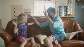 Un jeune père et sa petite fille heureuse mignonne se donnent de hauts fives se reposant sur le sofa Mouvement lent banque de vidéos