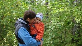 Un jeune père tient son enfant dans des ses bras Tendresse et étreinte du père aimé Activités en plein air clips vidéos