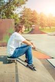 Un jeune patineur se reposant sur son conseil photo libre de droits
