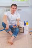 Un jeune peintre s'asseyant sur le plancher Photographie stock