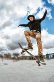 Un jeune planchiste transforme Wallie dans un skatepark, sautant sur une planche à roulettes en air avec un coup photos libres de droits
