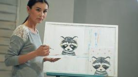 Un jeune professeur beau dessine sur un tableau noir, enseigne dans la classe d'art banque de vidéos