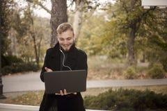 Un jeune sourire et homme heureux, tenant l'ordinateur portable ? disposition, communiquant avec quelqu'un images stock