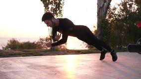 Un jeune sportif étant prêt pour sportif et la forme physique s'exerçant dehors Concept sain de mode de vie, homme faisant la pou banque de vidéos