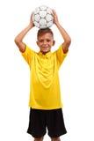 Un jeune sportif tient une boule au-dessus de son chef, un footballer dans l'uniforme de sports d'isolement sur un fond blanc Photos libres de droits