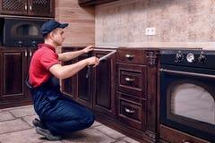Un jeune travailleur assemble les meubles en bois modernes de cuisine photographie stock