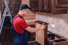 Un jeune travailleur installe un tiroir Installation des meubles en bois modernes de cuisine photo libre de droits