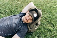 Un jeune type avec un sac à dos se trouve sur l'herbe et écoute la musique images stock