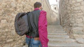 Un jeune type avec un sac à dos, un touriste, mène la fille derrière lui, tenant sa main le long de la rue médiévale à Gérone, l' clips vidéos