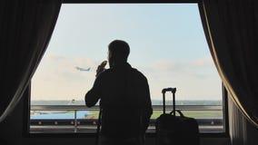 Un jeune type avec une banane dans des ses mains regarde l'avion décollant de la fenêtre de sa chambre d'hôtel et des feuilles av clips vidéos