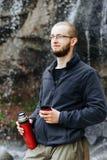 Un jeune type boit du thé ou du café d'un thermos, se tenant près d'une cascade dans les montagnes images libres de droits