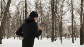 Un jeune type dans les espadrilles, les vêtements noirs de sports et un chapeau fonctionnant par la neige profonde en parc de vil banque de vidéos