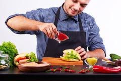 Un jeune type dans un tablier fait un hot-dog frais photos libres de droits