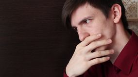 Un jeune type dans une chemise rouge touche ses lèvres avec les doigts de sa main droite, regards de doutes banque de vidéos
