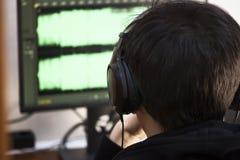 Un jeune type en grands plans rapprochés noirs d'écouteurs à un ordinateur manipule des voies de musique Créez les voies de musiq Photos stock