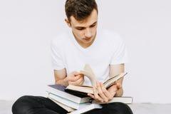Un jeune type est des livres de lecture Un étudiant, un écolier disposant à étudier Fond blanc d'isolement image libre de droits