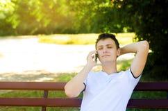 Un jeune type européen s'assied sur un banc en parc et parle au téléphone, jetant son bras derrière sa tête et fermeture le sien photos stock